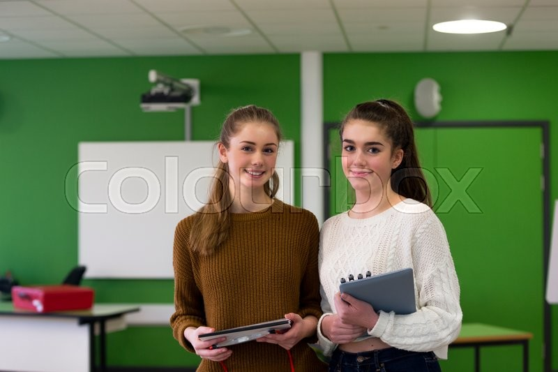 Stock image of 'Two teenage girls standing together in a classroom with school eqipment in their hands. '