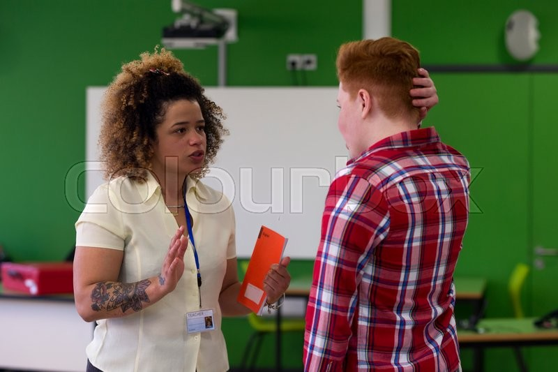 Stock image of 'Teenage student being told off by his English teacher at school. '