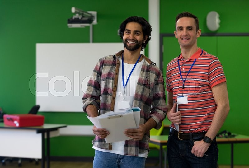 Stock image of 'Two male teachers standing together with paper work and a digital tablet. They are smiling and looking at the camera.'