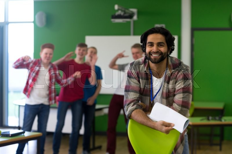 Stock image of 'School teacher is smiling for the camera. A group of teenage boys are in the background making sneaky, silly faces at the camera.'