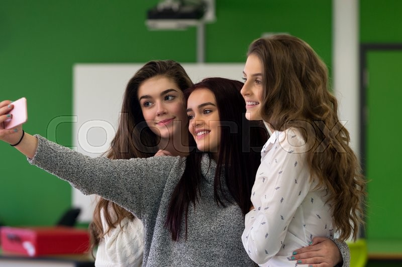 Stock image of 'Three female students taking a selfie together on a smartphone in a classroom.'