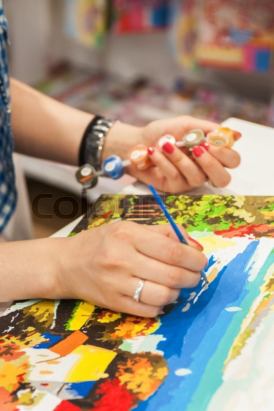 Stock image of 'woman is painting anti stress adult coloring book -special picture with paints   '