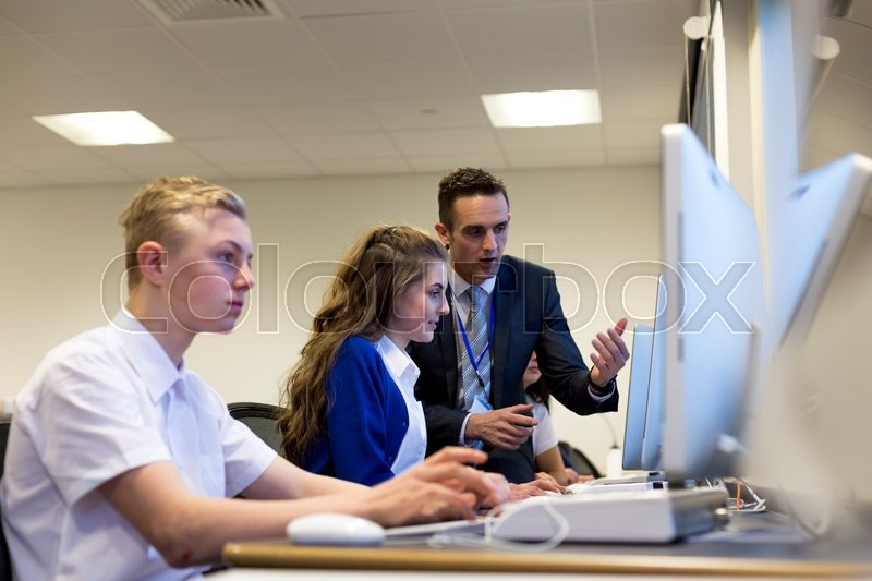 Stock image of 'Male teacher helping one of his students who is working on a computer.'