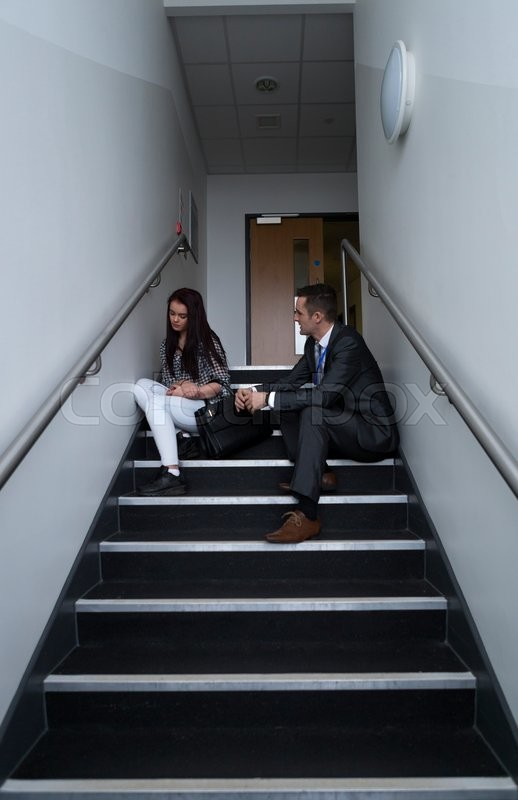Stock image of 'Female student is sitting on the stairs in her school, with her teacher next to her. He is telling her off for her behaviour.'