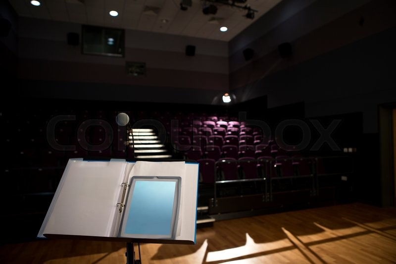 Stock image of 'Empty lecture hall with a digital tablet on the podium.'