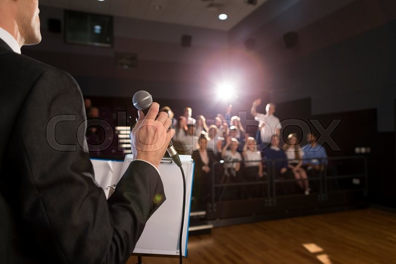 Stock image of 'Male teacher making a speech in a lecture hall. He is standing at the podium and some students have their hand up to ask a question. '
