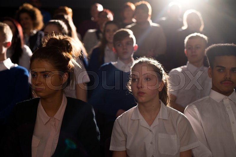 Stock image of 'Crowd of teenage students in a lecture hall. They are looking towards the speaker, who can't be seen.'
