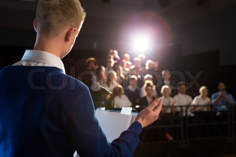Stock image of 'Male student making a speech. He is standing at the podium and is talking to the crowd of people.'