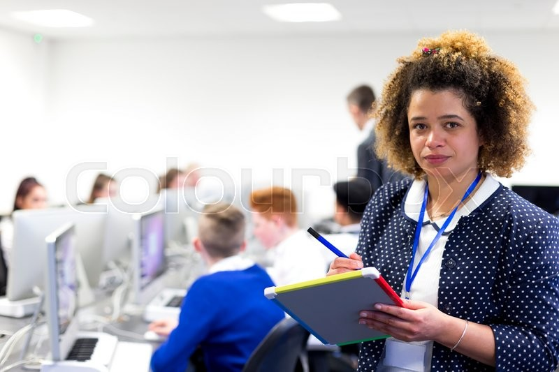 Stock image of 'Teacher standing in a classroom with a whiteboard and pen. She is looking at the camera. Students are working on computers in the background.'