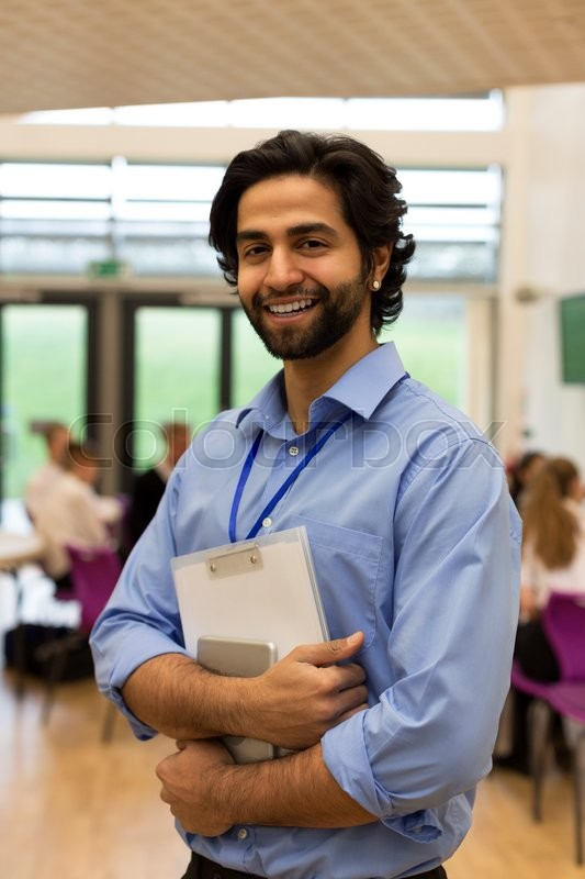 Stock image of 'Waist up portrait of a school teacher. He is holding some paperwork and a digital tablet.'