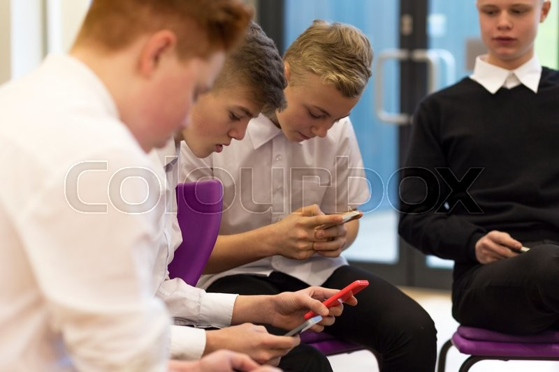 Stock image of 'Group of male high school students on their break at school. They are all looking at smartphones.'