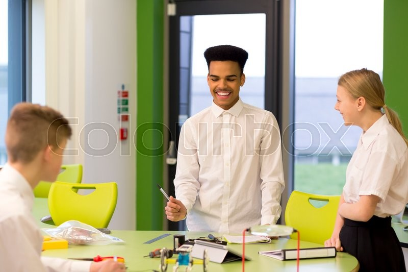 Stock image of 'Three students are chatting and laughing whilst building robotic arms in technology class.'