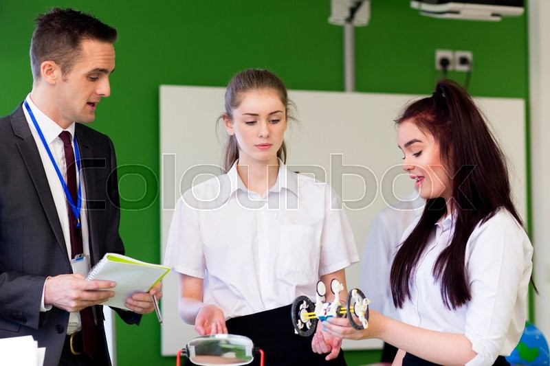 Stock image of 'Teacher discussing some work with two teenage students.'