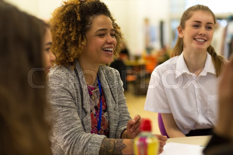 Stock image of 'Young female teacher having a laugh with her students during lesson.'