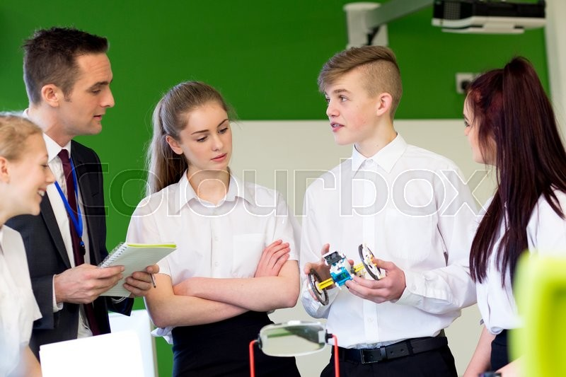 Stock image of 'Group of students having a discussion with their teacher about something they have built in their Design and Technology lesson.'