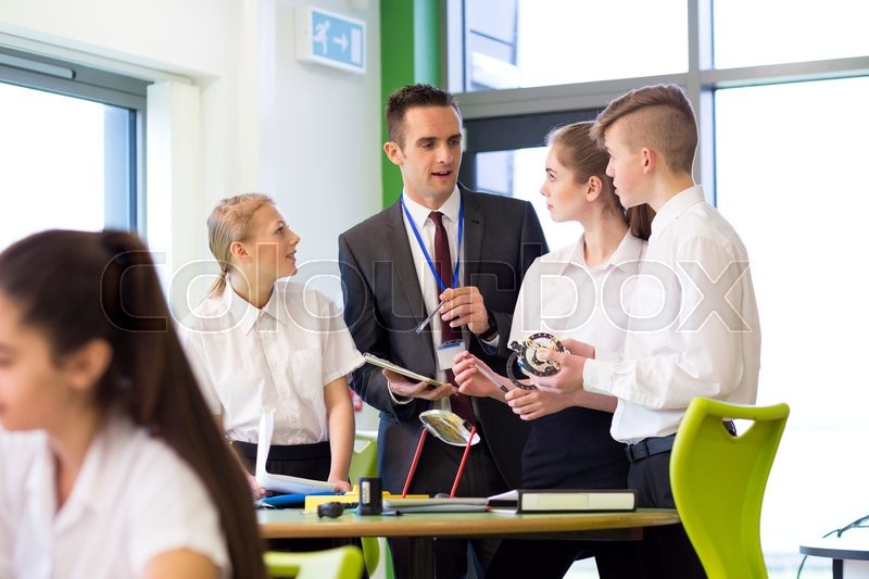 Stock image of 'Small group of students discussing their work witht the head teacher in the classroom.'