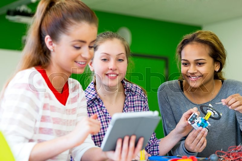 Stock image of 'Students working together with a digital tablet to build a robot in a classroom.'