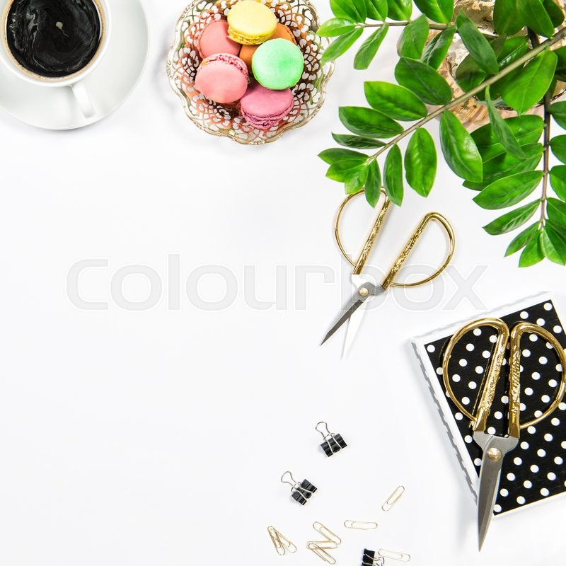 Stock image of 'Feminine workplace with coffee, macarons cookies, office supplies and green plant on white table background. Flat lay'