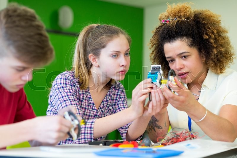 Stock image of 'Teacher helping two students build a robotic arm in their design and technology lesson'