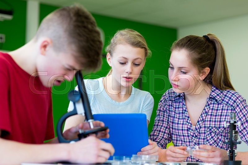 Stock image of 'Students in a science lesson are using a microscope to look at cells. They are using a digital tablet to research.'