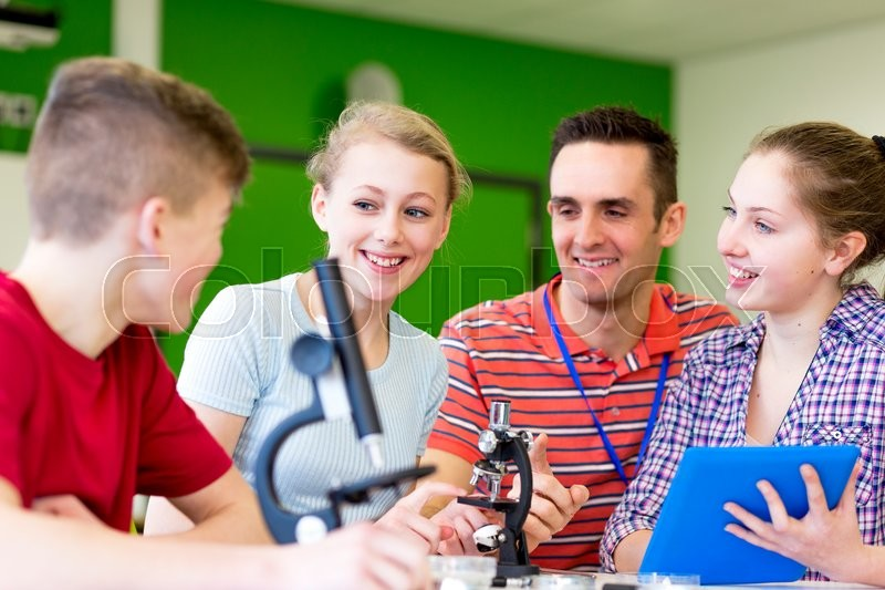 Stock image of 'Teacher is supervising his students as they experiment with microscopes'