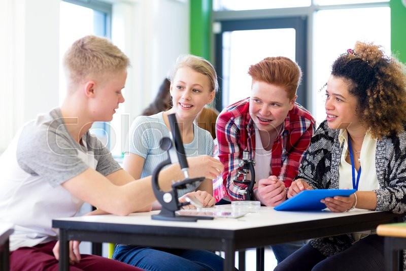 Stock image of 'Students sitting with teacher in a lesson. They are using microscopes and a digital tablet.'