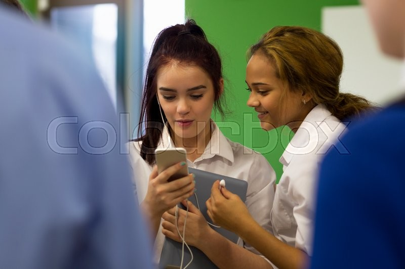 Stock image of 'Two students sharing headphones which are connected to a smartphone. they are watching the screen of the phone and have a digital tablet with them. '