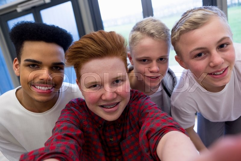 Stock image of 'Four teenage students taking a selfie in school.'
