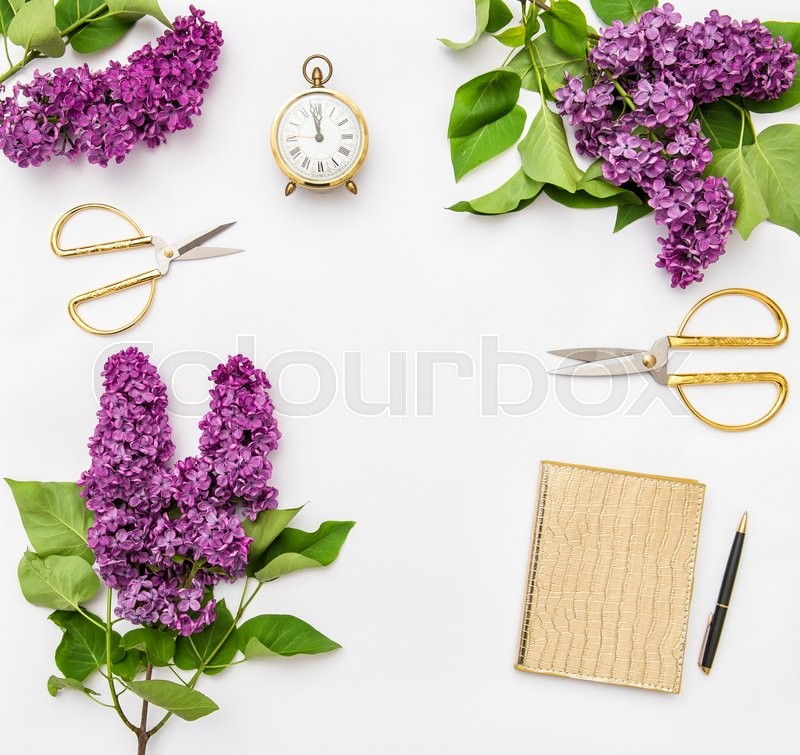 Stock image of 'Lilac flowers, diary notebook, golden office supplies. Flat lay'