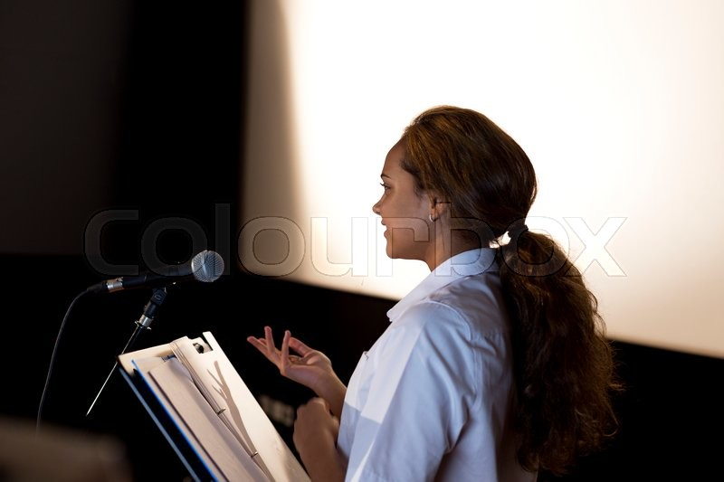 Stock image of 'Female student making a speech. She is standing at a podium and talking to the crowd.'