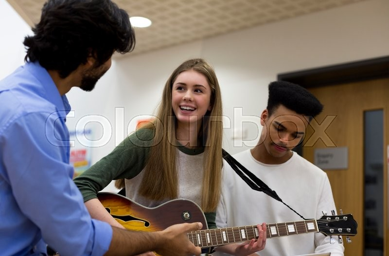 Stock image of 'Music teacher helping students learn to play guitar. '