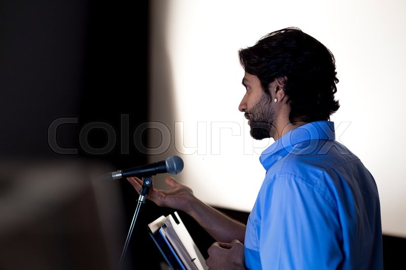 Stock image of 'Male teacher making a speech in a lecture hall. He is standing at the podium and smiling to the crowd.'