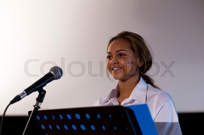 Stock image of 'Female student making a speech. She is standing at a podium and smiling to the crowd.'