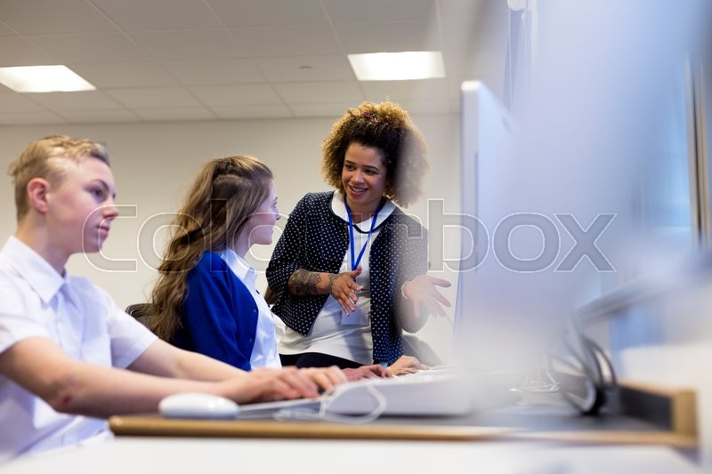 Stock image of 'Teacher with student in a computer lesson. She is explaining something on the students computer.'