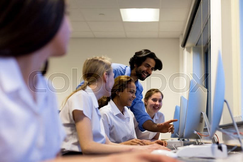 Stock image of 'Teacher with students in a computer lesson. They are all looking at a screen and laughing.'