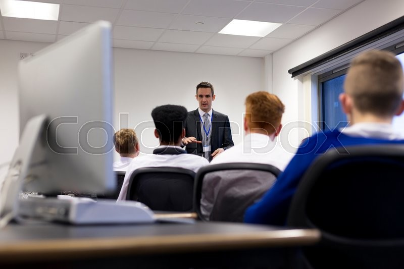 Stock image of 'Teacher talking to student group in a lesson.'