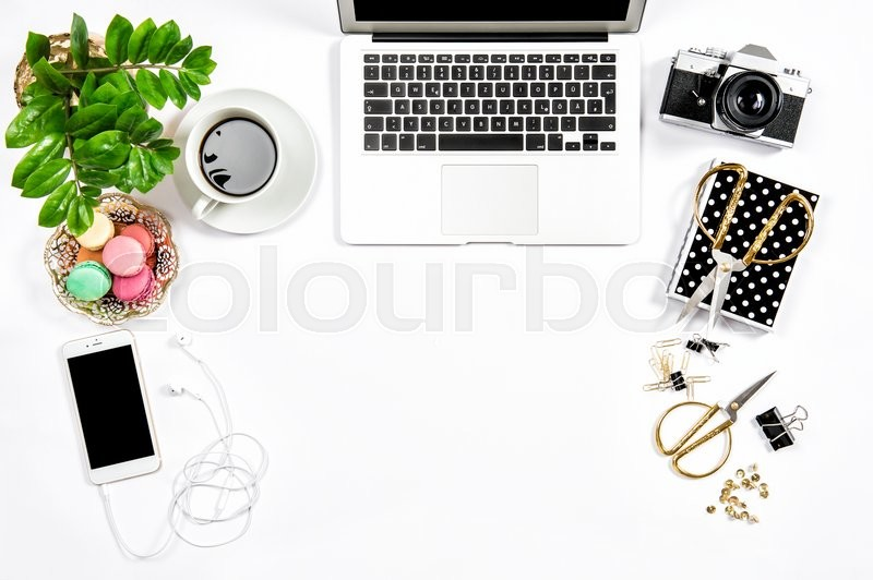 Stock image of 'Feminine workplace still life. Coffee and macaroon cookies. Office supplies and laptop'