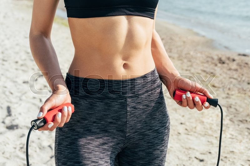 Stock image of 'Close-up of a girl with a flat stomach with a skipping rope in her hands on the beach'