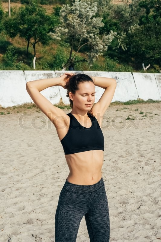 Stock image of 'Young slim girl in sportswear doing morning exercises at the beach in summer, vertical framing'