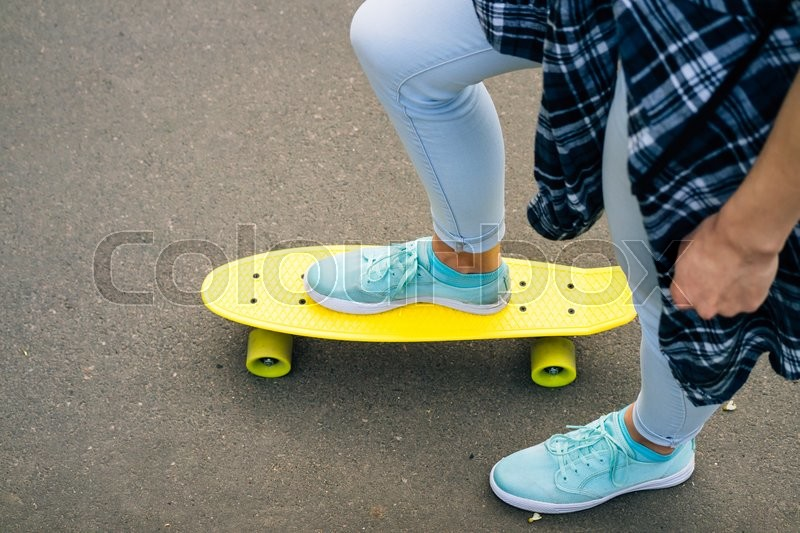 Stock image of 'Top view of female legs in jeans and sneakers on yellow skateboard'
