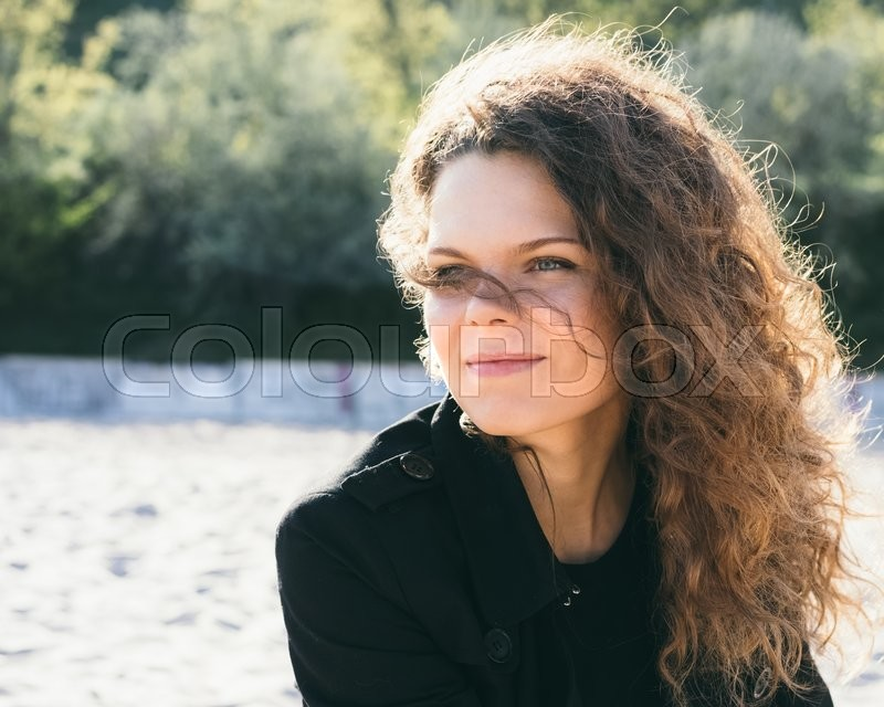 Stock image of 'Portrait of a beautiful smiling brunette with curly hair in a coat at the beach'