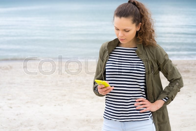 Stock image of 'Young girl in a green jacket uses yellow mobile phone on the beach'