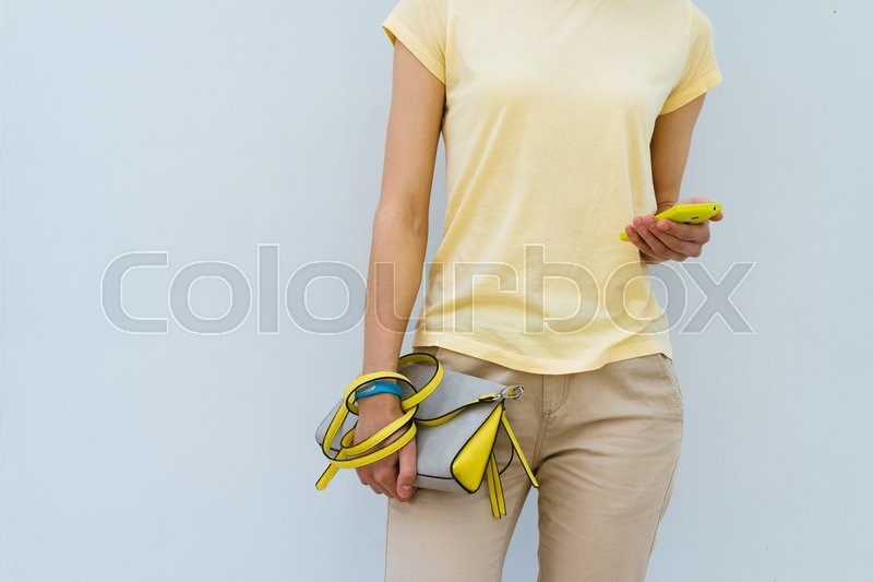 Stock image of 'Slender girl in a yellow T-shirt holding yellow lady's handbag and mobile phone'