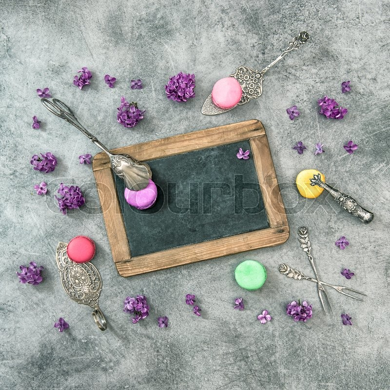 Stock image of 'Macaroon cookies with lilac flowers. Antique kitchen utensils and chalkboard. Vintage style toned picture'