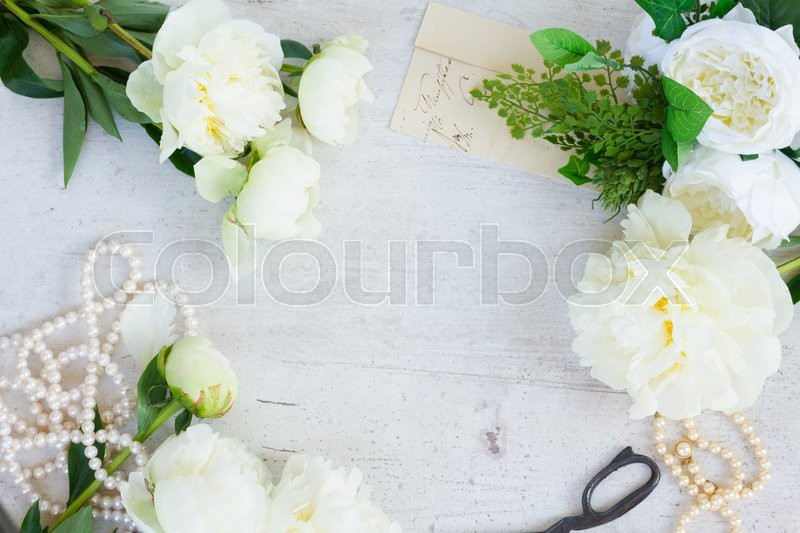 Stock image of 'White fresh peony flowers with pearls jewellery on white wooden table frame with copy space'