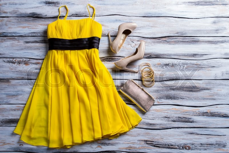Stock image of 'Yellow dress, purse and shoes. Casual yellow dress with accessories. Lady's charming summer outfit. New clothes and heel shoes.'