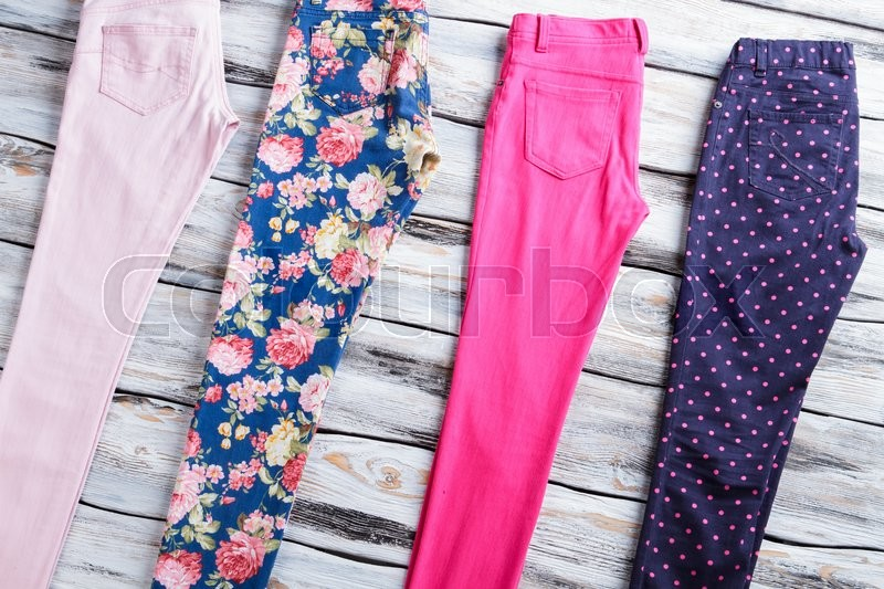 Stock image of 'Casual trousers of different color. Navy and pink pants. Female pants on wooden table. Choose what suits you best.'
