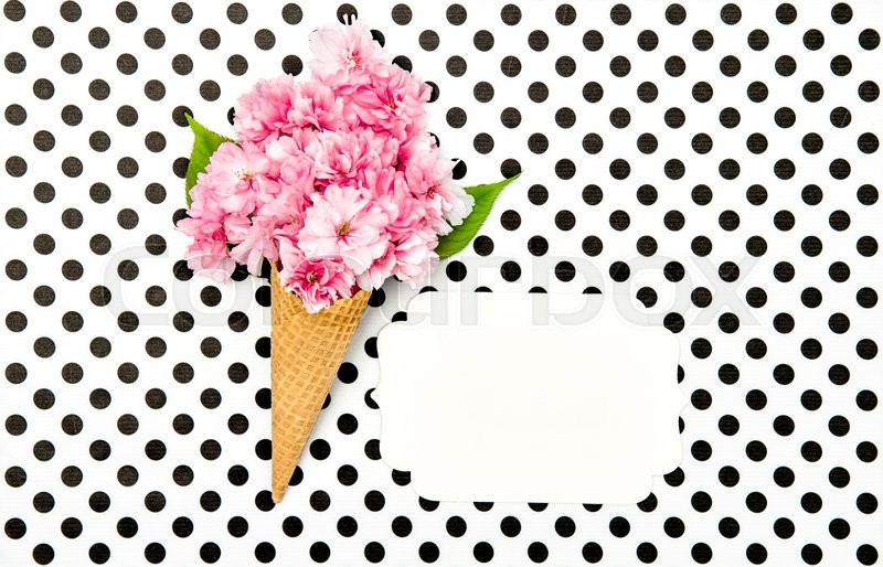 Stock image of 'Cherry tree flowers in ice cream waffle cone on polka dot background. Flat lay. Minimal concept. White paper tag for your text'