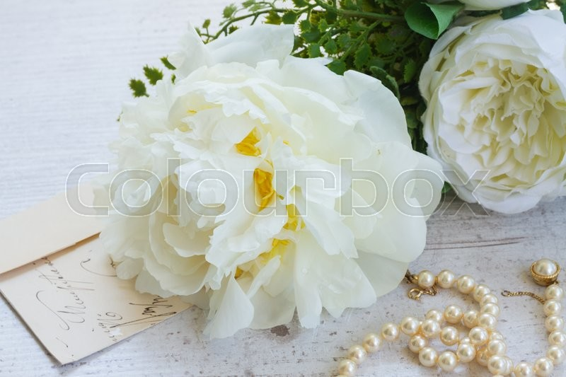 Stock image of 'White fresh peony flowers with pearls jewellery close up on white wooden table'