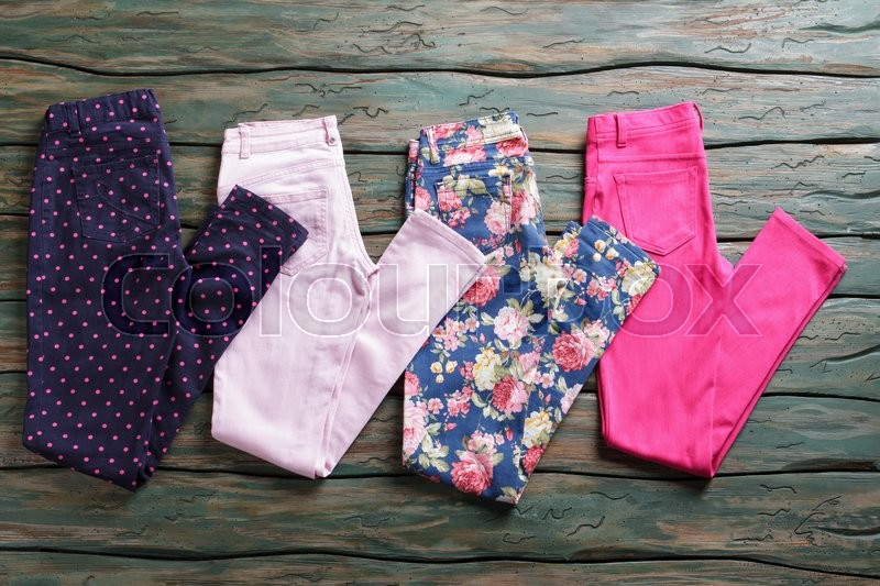 Stock image of 'Dark trousers with dotted print. Colorful pink folded pants. Discounted goods in outlet shop. Last sizes at special price.'